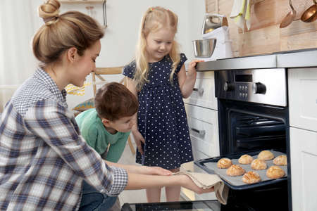 Mother and her children taking out cookies from oven in kitchen 版權商用圖片