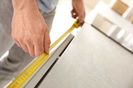 Man measuring kitchen furniture indoors, closeup. Construction tool