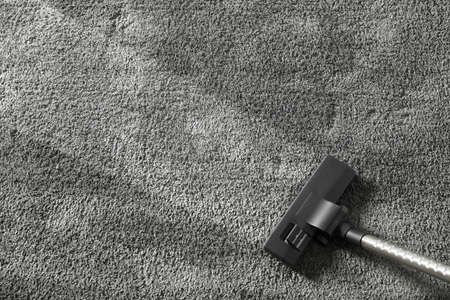 Removing dirt from grey carpet with vacuum cleaner, top view. Space for text