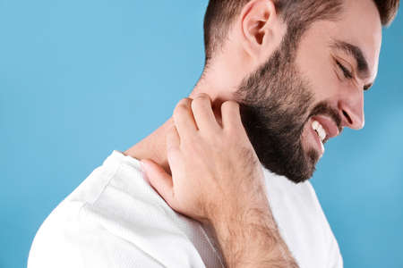 Young man scratching neck on color background. Allergies symptoms