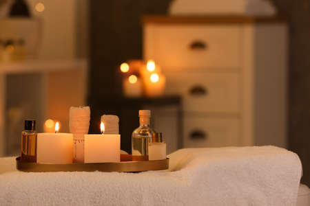 Cosmetics and burning candles on massage table in spa salon, space for text