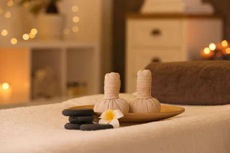 Herbal compresses and stones on massage table in spa salon