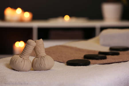 Herbal compresses and stones on massage table in spa salon. Space for text