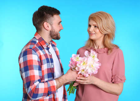 Young man congratulating his mature mom on color background. Happy Mothers Day