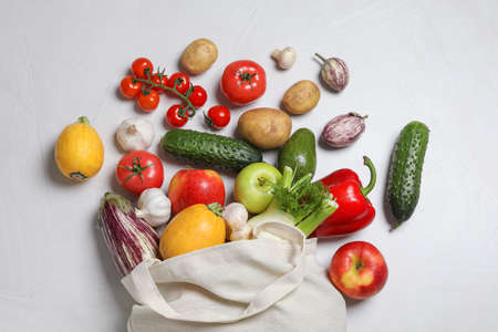 Bag with fresh vegetables and fruits on light background, flat lay