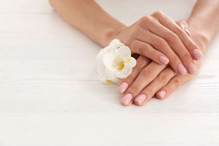 Closeup view of woman with flower at white wooden table, space for text. Spa treatment
