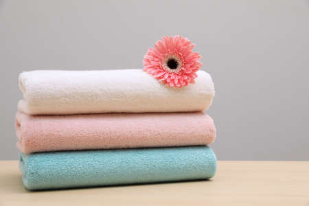 Stack of fresh towels with flower on table