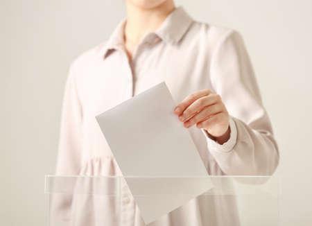 Femme mettant le vote dans l'urne sur fond clair, gros plan