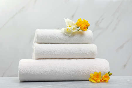 Stack of fresh towels with flowers on grey table against light background