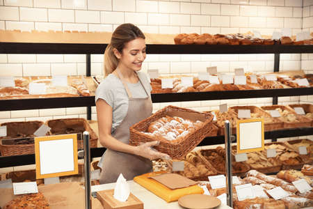 Woman with wicker tray of pastry in bakery shop