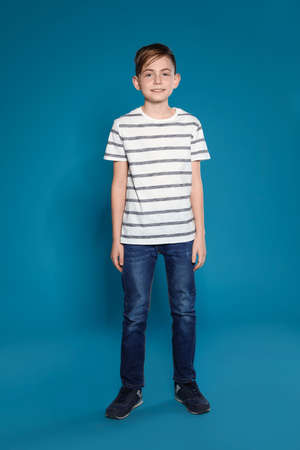 Full length portrait of cute boy on color background