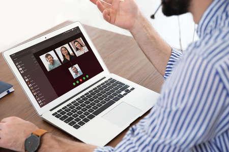 Mężczyzna rozmawiający na czacie wideo z kolegami przy stole w biurze, zbliżenie