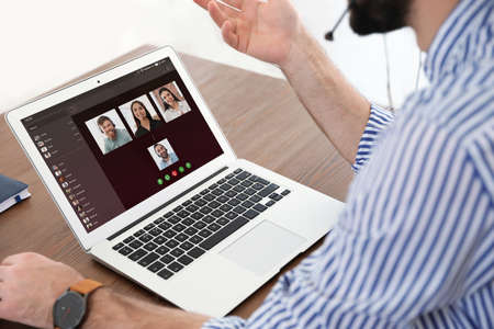 Man having video chat with colleagues at table in office, closeup Imagens - 122285030