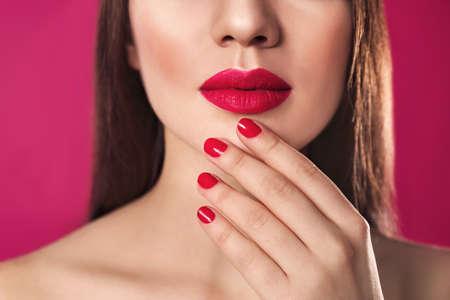 Beautiful woman with stylish nail polish on color background, closeup