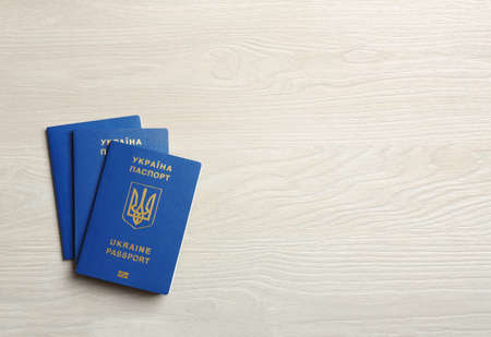 Ukrainian travel passports on wooden background, top view with space for text. International relationships
