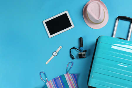 Flat lay composition with suitcase and accessories on color background, space for text. Summer vacation