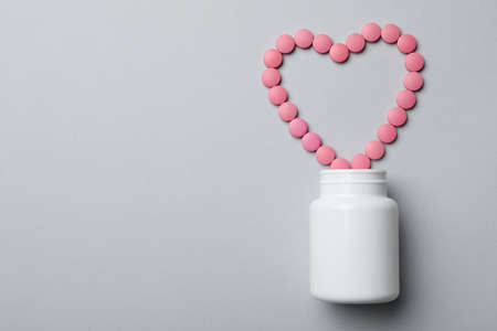 Bottle and heart of pills on grey background, flat lay. Space for text 免版税图像