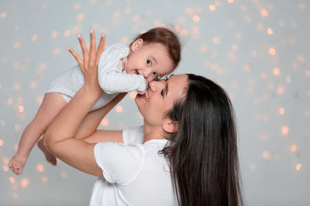 Young mother with her cute little baby against defocused lights 版權商用圖片