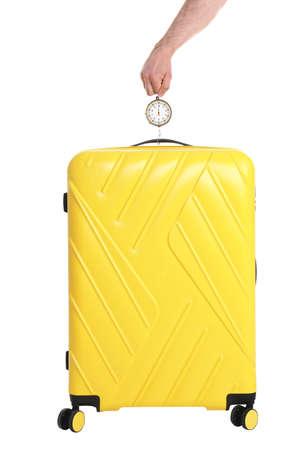 Man weighing stylish suitcase on white background