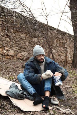 Poor homeless man sitting on cardboard in city park