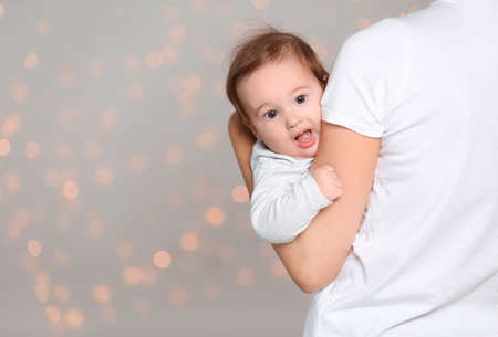 Young mother holding cute baby against  defocused lights. Space for text