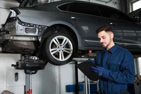 Technicien vérifiant la voiture sur l'ascenseur hydraulique à l'atelier de réparation automobile
