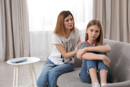 Mère inquiète parlant à sa fille adolescente à la maison