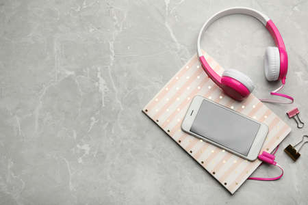 Composición plana con auriculares y teléfono inteligente en la mesa. Espacio para texto