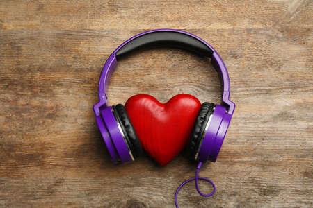 Coeur décoratif avec des écouteurs modernes sur fond en bois, vue de dessus