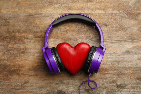 Decorative heart with modern headphones on wooden background, top view