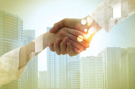 Business partners shaking hands against cityscape, closeup. Double exposure