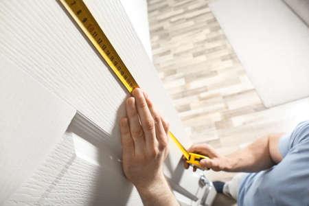 Man measuring door in room, closeup. Construction tool
