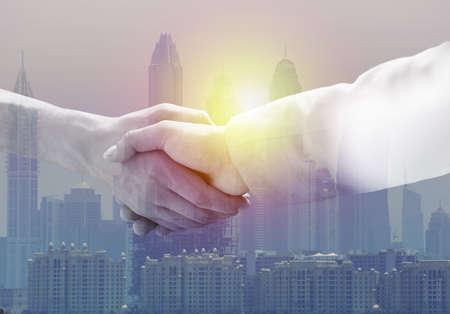 Businessmen shaking hands against cityscape, closeup. Double exposure Imagens
