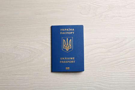 Ukrainian travel passport on wooden background, top view. International relationships