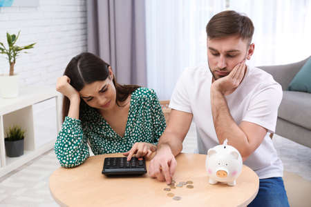 Unhappy young couple with piggy bank and money at home. Financial problems 免版税图像