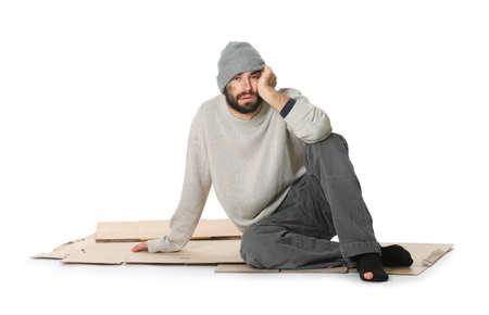 Poor homeless man sitting on cardboard, white background Stock Photo