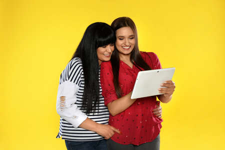 Young daughter and her mature mother with tablet computer on color background
