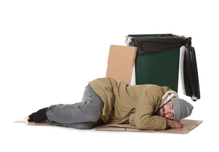 Poor homeless man lying near trash bin isolated on white background