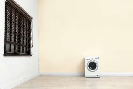 Washing machine near color wall in empty room, space for text. Laundry day
