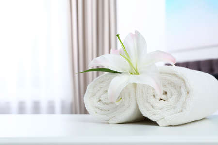 Rolled towels and flower on table in bedroom. Space for text