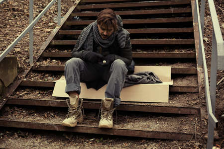 Poor young man sitting on stairs outdoors