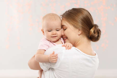 Portrait of happy mother with her baby against blurred lights