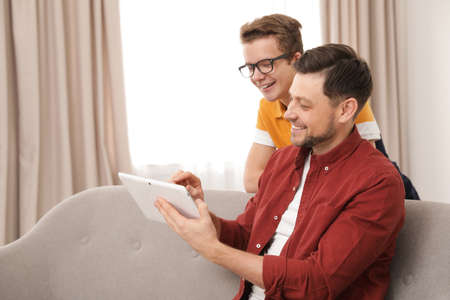 Happy father and his teenager son with tablet computer at home Stock Photo