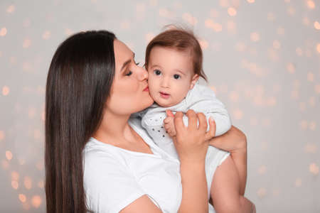 Portrait of young mother and her adorable baby against defocused lights