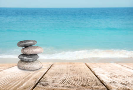 Stacked zen stones on wooden pier against sea, space for text Banque d'images