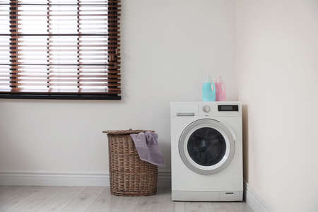 Modern washing machine and laundry basket indoors