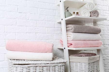 Estantería y cestas con toallas limpias y artículos de tocador cerca de la pared de ladrillo