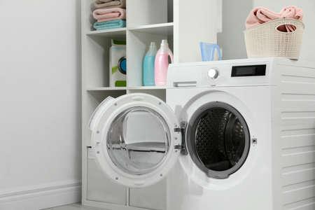 Lavadora moderna en el interior de la sala de lavandería