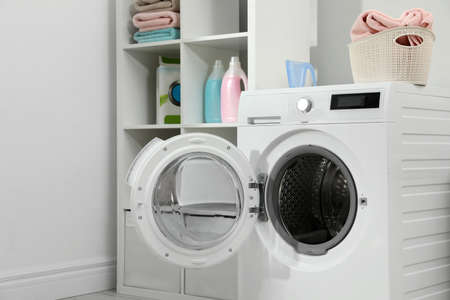 Modern washing machine in laundry room interior