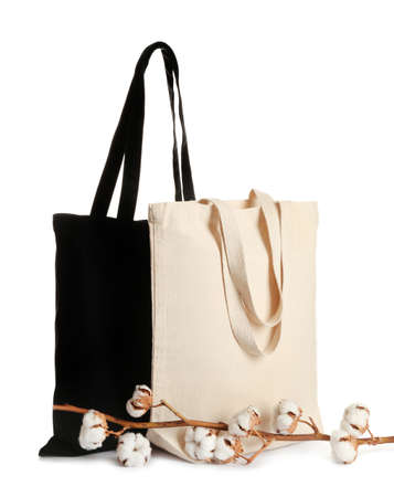 Stylish eco bags and cotton flowers on white background Foto de archivo